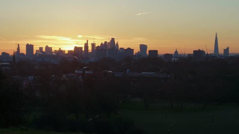 London skyline at sunrise from Primrose Hill in Regents Park. Famous landmarks include the St Paul's Cathedral and the skyscrapers of the the City of London