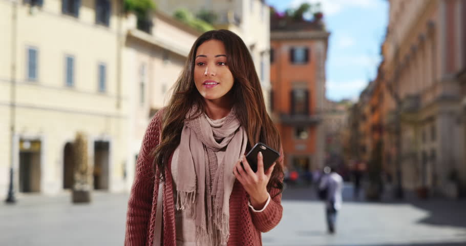 Smiling Latina woman with her phone waving to a friend. Portrait of happy attractive woman smiling and saying hi. 4k | Shutterstock HD Video #1007732131