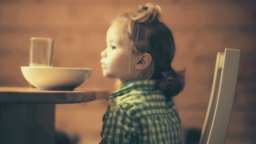 Kitchen, children appetite, food for child. Cute kid does not want to eat porridge. Healthy Eating Cuisine. Childish whim, sweet boy asks for food. Light supper in wooden house. Healthy childhood
