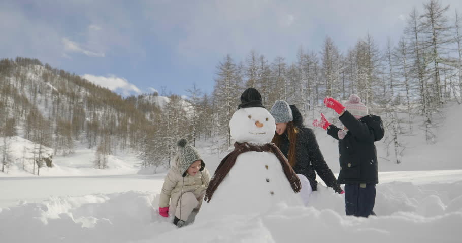 On a winter day, in the mountains with snow, a family plays the snowman together. Concept of: winter holidays, family, christmas, mountain