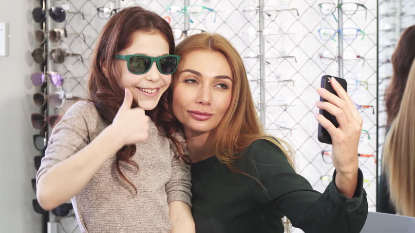 Gorgeous woman taking selfies with her cute little daughter while shopping for sunglasses at eyewear store optometrist optics family bonding technology social media lifestyle consumerism buying. #1007745181