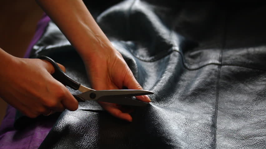 The woman is cutting the sheepskin coats. He cuts the sheepskin with a pair of sheepskin coats and spreads the cut.