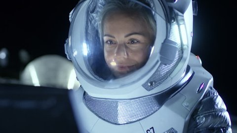 Female Astronaut Wearing Space Suit Works on a Laptop, Exploring Newly Discovered Planet, Communicating with the Earth. In the Background Living Station. Colonization Concept. Shot on RED EPIC-W 8K