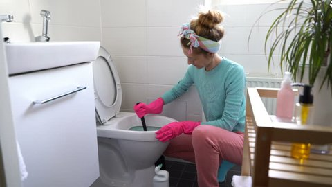 Woman with a rubber glove cleans a toilet bowl using means for cleaning