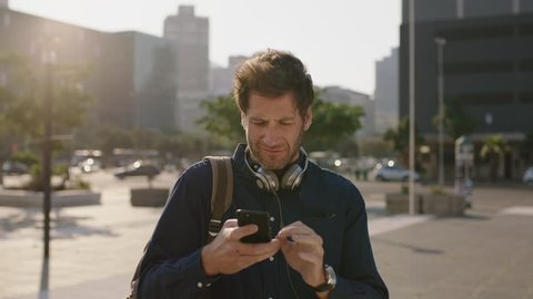portrait of handsome young caucasian man looking lost checking map on smartphone in city