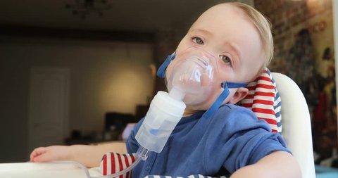 Inhalation child 1,5 year nebulizer mask vapor. The weakened kid is sick in the home interior