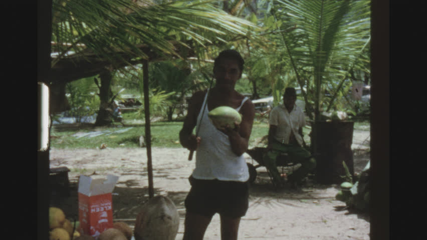 JAMAICA, MAY 1971. Two Shot Sequence. Male Jamaican Cutting And Preparing A Coconut For An Audlt Female German Tourist
