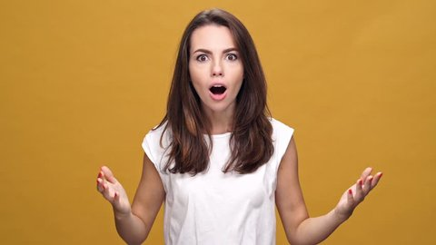 Young shocked surprised woman standing isolated over yellow background while looking camera