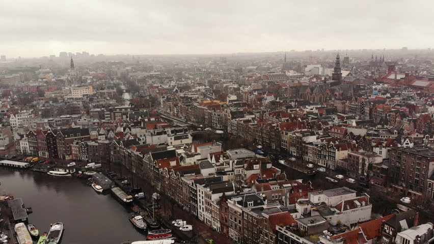AMSTERDAM, NETHERLANDS February 18, 2018: The camera flies in an aerial shot over Amsterdam and its canals to the Oude Kerk.