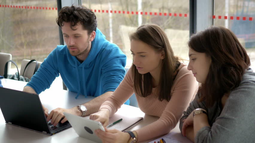 Group of students preparing for a presentation at the university. Friends studying together and discussing about the topic. | Shutterstock HD Video #1007839021