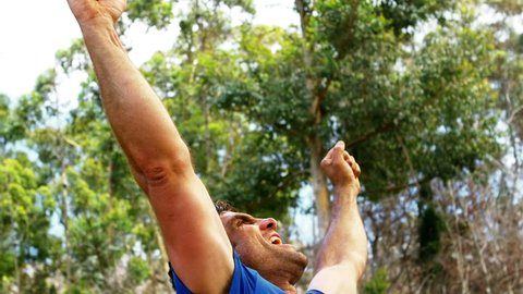 Close-up of happy man raising his hands and smiling at boot camp