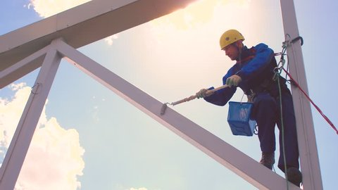 The industrial climber works at a height, painting metal structures located on the roof of the building.