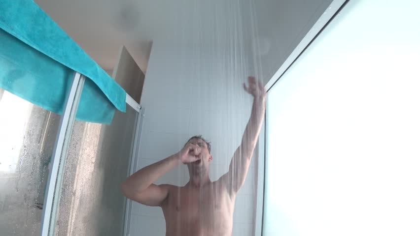 young handsome muscular man takes a shower. the guy washes, sings and dances in the shower. action camera.