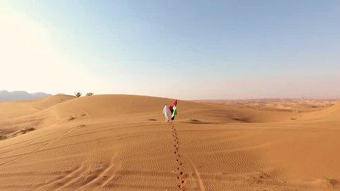 Proud arabian Emirati man holding a UAE flag, walking in the desert