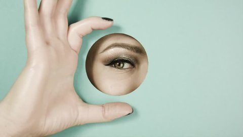 Girl's eye with beautiful make-up,with sparkles,with shadows, peeps through circular crevice of colored paper. The girl playfully peeping through hole. Her palm makes binoculars. Concept advertising.