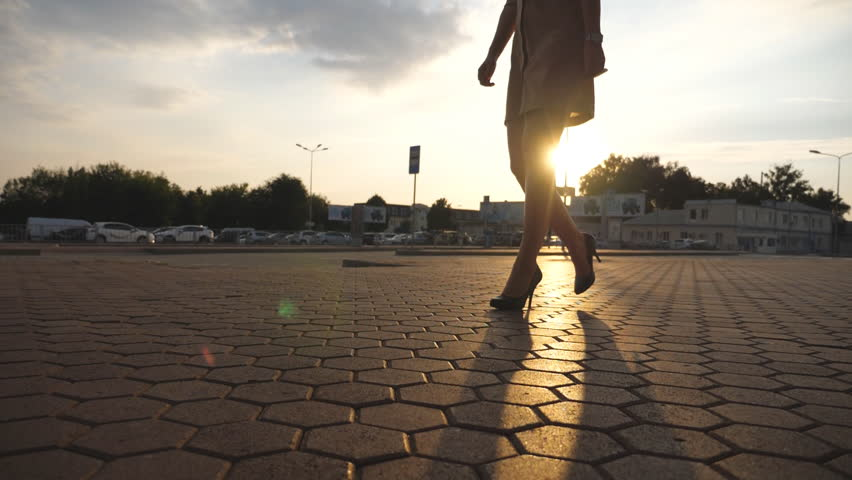 Female legs in high heels shoes walking in the urban street at sunset. Feet of young business woman in high-heeled footwear going in the city with sun flare at background. Girl stepping. Slow motion #1007928601