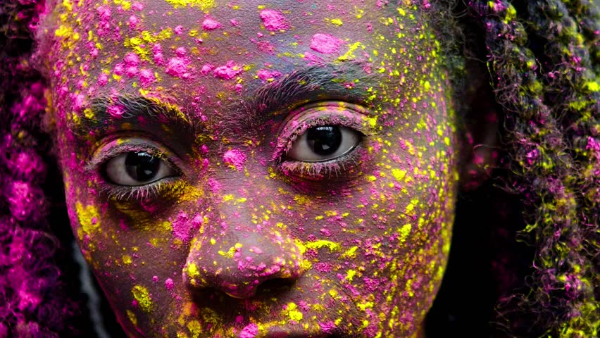 African woman with coloufrul powder on her face and body