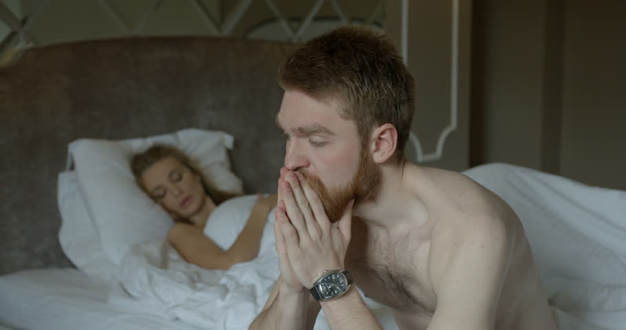 Couple is having problems in bed. The upset ginger head man is worrying and sitting on the bed while his angry blonde lover in thong is leaving the room.