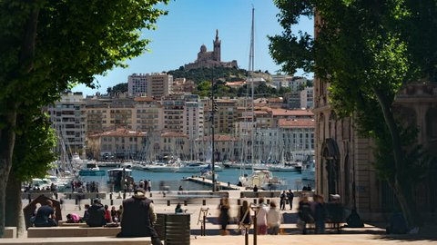 Timelapse - Crowds on city steps at the old port looking over to Basilica de Notre Dame de la Garde in summer