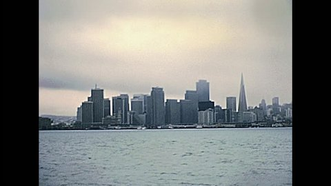 San Francisco Oakland Bay Bridge from Treasure Island with San Francisco cityscape with Transamerica building and Coit tower in an archival footage in 1980s. California, United States in year 1980.