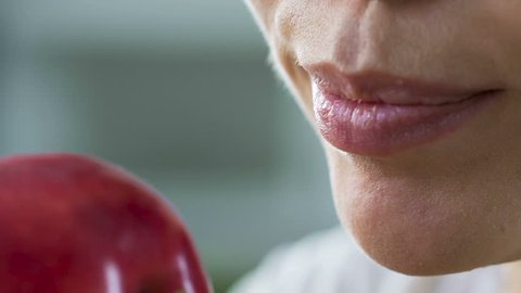 Woman biting red juicy apple by healthy teeth, source of vitamins and calcium