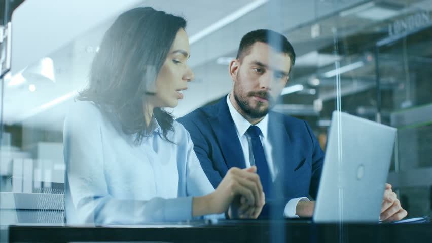 Female Accountant and Male Businessman Sitting at the Desk Having Discussion and Working on a Desktop Computer, Solving Problems. Modern Stylish Office with Beautiful People. Shot on RED EPIC-W 8K.