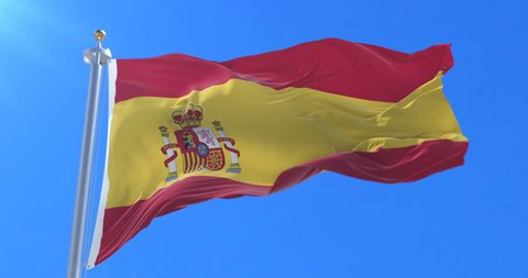 Spain flag waving at wind with blue sky in slow, loop