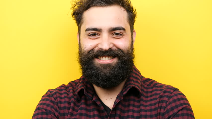 Happy smiling long bearded hipster winking silly on yellow background