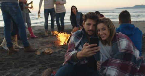 Couple enjoying bonfire with friends on beach