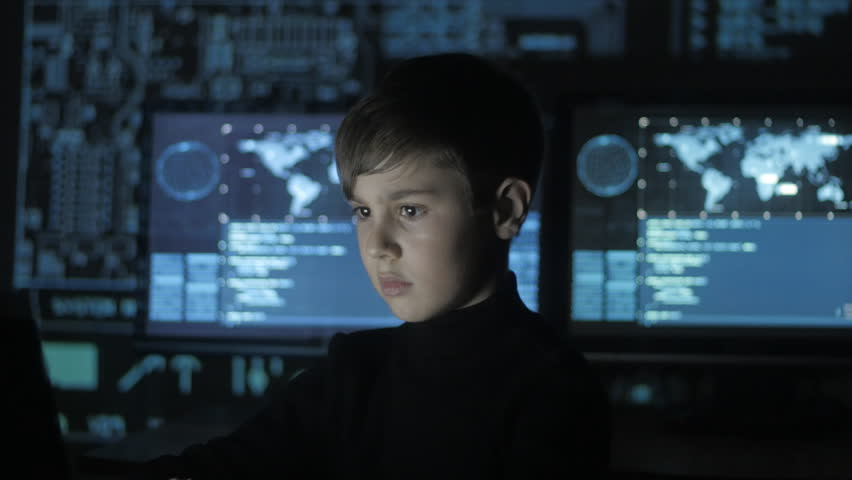 young prodigy boy hacker programmer working at the computer in the data center filled with display screens. Portrait of Child prodigy hacker.