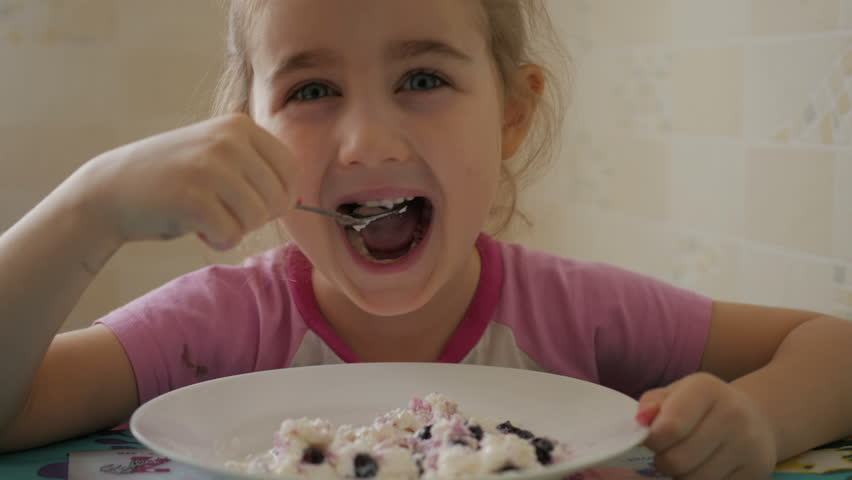 A child eats a curd dessert with currant berries. A little girl is eating cottage cheese.