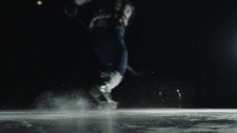Ice Hockey player performing slap shot isolated on black background close up