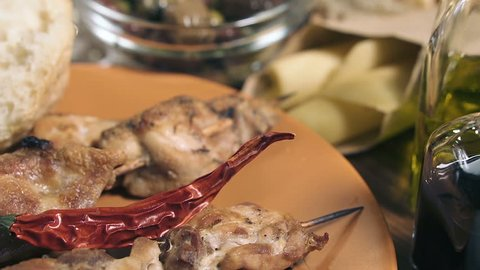 Close-up of grilled chicken meat, bowl with different kind of olives, glass of wine, cheese and fresh bread ciabatta on the wooden table, panning shot.