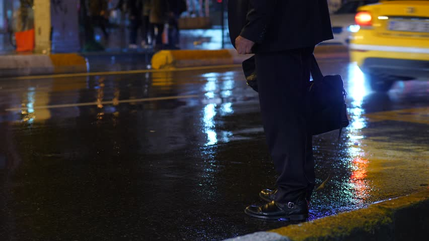 Businessman stay on wet road, legs view, cars quickly sweep past. Man turn and walk away, can not catch free taxi at busy night time. Water covering roadway after rain
