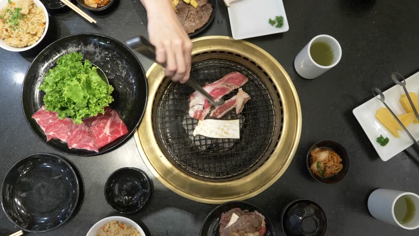 Korean barbecue grill. people cook and eat dishes cooked on a Korean grill in a restaurant. 4k, close-up.
