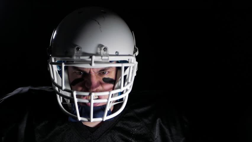 american football player in front of black background in slow motion #1008116911