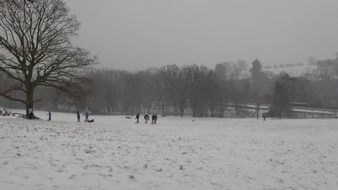 Children tobogganing on Chorleywood Common, Hertfordshire, UK