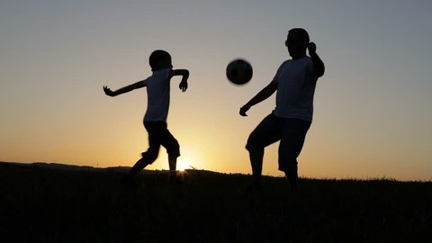 Father and son playing soccer in the park at the sunset time. People having fun outdoors. Concept of friendly family.