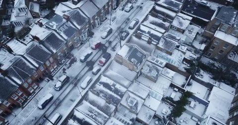 Top down drone footage of a road in South West London, England, UK during a rare snow storm in March 2018.