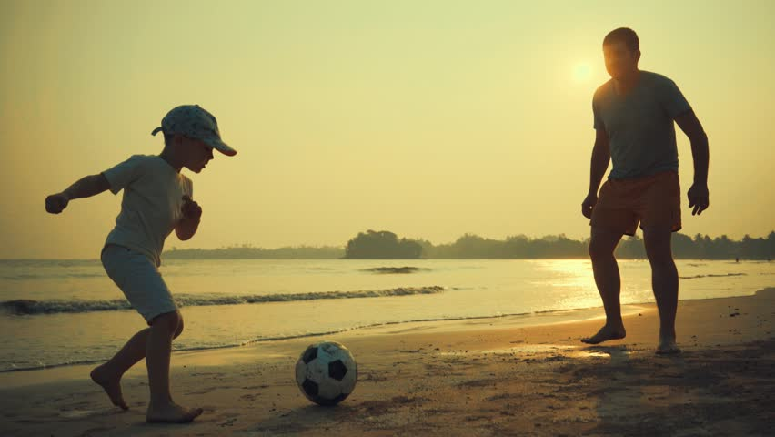 Father and son playing together with ball in football on the beach under sunset background #1008146251