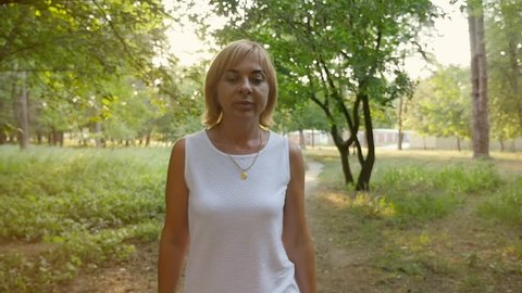 A wonderful view of a dreamlike blonde woman in a sleeveless white dress moving forward in a romantic park in summer in slow motion