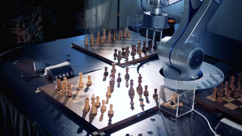 A robotic arm is moving chess pieces and pressing the chess clock
