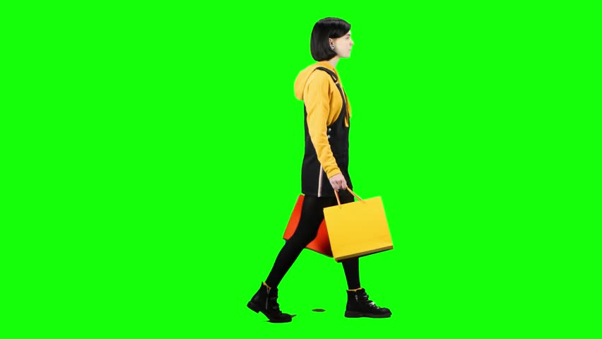 Teenage girl with packages is walking down the street. Green screen. Side view
