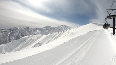 Winter mountains with snow, clouds and sunshine. Hakuba 47 filmed from top chair lift. Happo. Japan.