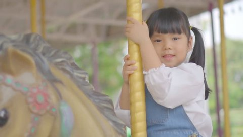 Asian children cute or kid girl enjoy smile and happy fun with riding horse or playing carousel in amusement park on summer holiday relax and family vacation on slow and soft tone