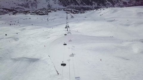Drone view of a ski lift with people skiing underneath