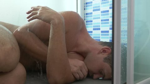 the man in the shower became ill, he fell to the floor, the water was pouring on him. 4k. Slow motion
