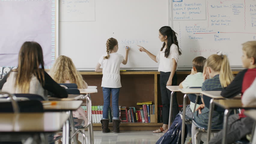 Teacher watching girl solving math equation on classroom whiteboard / Provo, Utah, United States