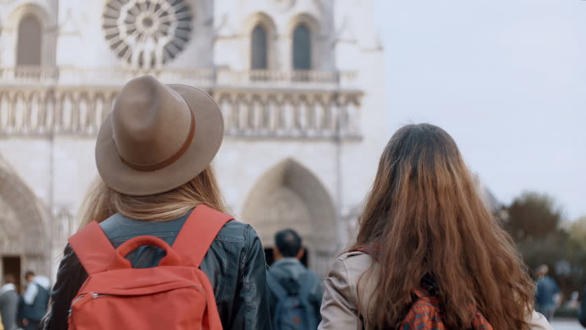 Back view of two traveling woman with backpack walking near the Notre Dame, famous cathedral in Paris, France. | Shutterstock HD Video #1008239191