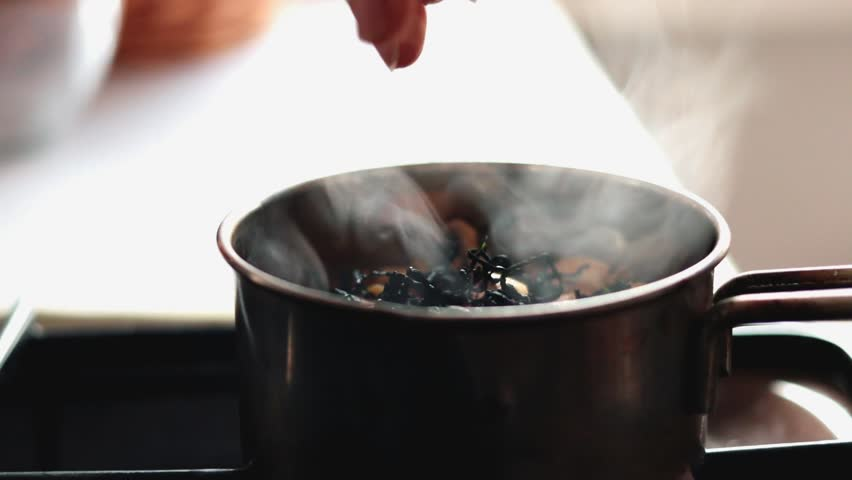 Hand adds seaweed as a salt. Buckwheat cooks in metal pot on gass cooker stove lighter. Boiling water with mushrooms.  Lunch. Russian traditional porridge. Raw, vegan, vegetarian healthy food concept.